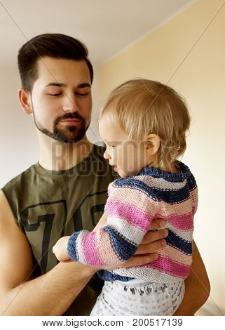 Father holding his baby daughter at home.