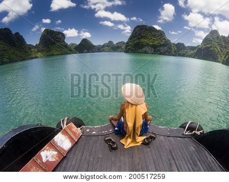man wearing a Vietnamese hat enjoying the magnifiecent sight of Ha Long bay limestone rocks on a beautiful sunny day during a boat cruise, Vietnam