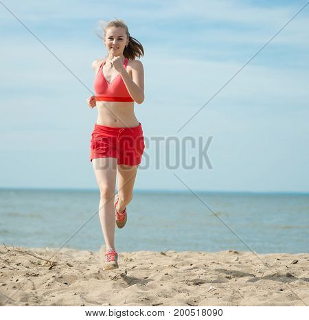 Young lady running. Woman runner running at the sunny summer sand beach. Workout near ocean sea coast. Beautiful fit girl. Fitness model caucasian ethnicity outdoors. Weight loss exercise. Jogging.