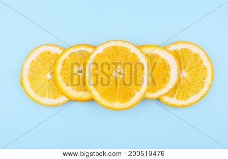 Fresh fruit in a cut on blue background. Pattern of citrus fruits. Diet and healthy food concept. Flat lay style.