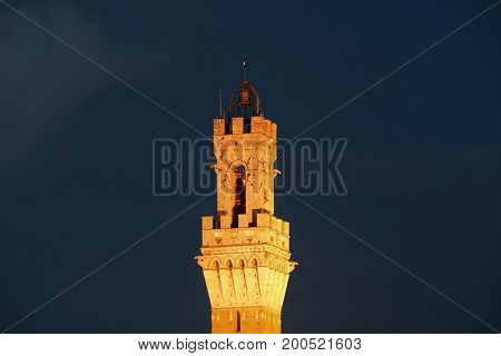 City Hall Bell Tower closeup at night in Siena Italy.