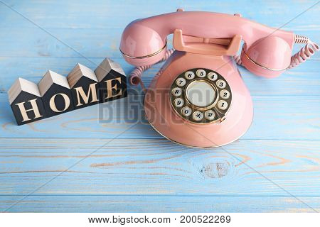 Pink Retro Telephone With Word Home On Blue Wooden Table