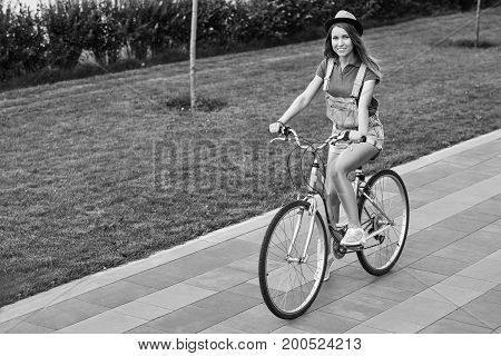 Monochrome shot of a happy young beautiful woman enjoying riding her bike outdoors at the local park copyspace youth happiness emotions freedom recreation enjoyment beauty carefree.