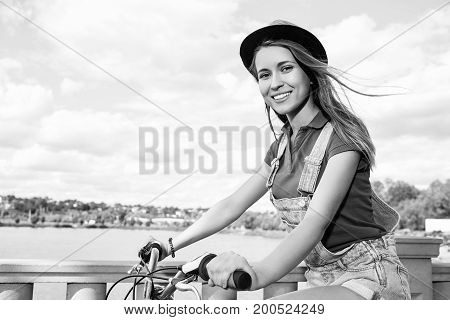 Monochrome shot of a gorgeous young active woman smiling happily while cycling at the local park copyspace biker riding rider cyclist bicyclist sport activity fitness happiness concept.