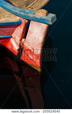 Red rudder of an old fishing boat and its reflection in a water