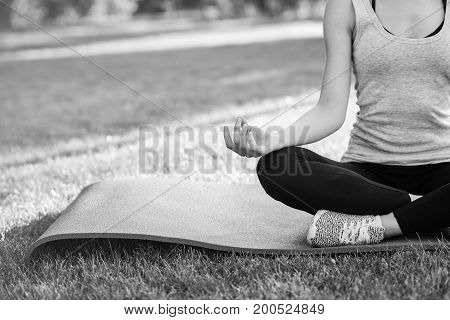 Monochrome cropped shot of a sportswoman sitting on lotus position relaxing and meditation outdoors at the local park copyspace calamity peaceful tranquil harmony.