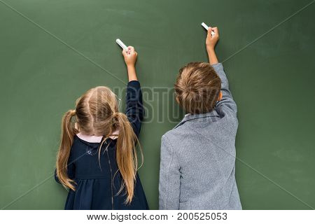 two adorable pupils writing on green chalkboard