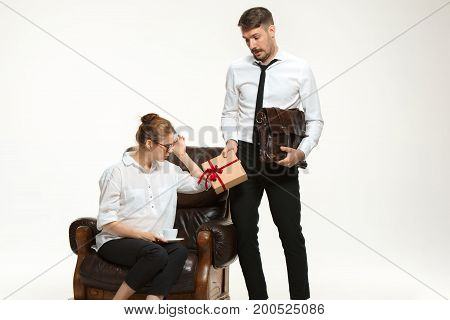 The young man with gift and beautiful woman at office isolated on white background. Concept of boss and subordinate