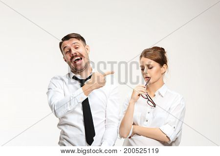 The young man and beautiful woman in business suits at office isolated on white background. Concept of boss and subordinate. One man ridicules another