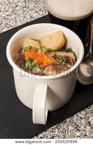 dublin coddle an irish specialty in a mug on slate