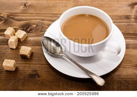 coffee with milk and brown sugar on a wooden table