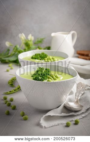 Green pea soup in bowls on grey concrete or stone background, selective focus
