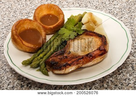 yorkshire pudding pork chop and green asparagus on a plate