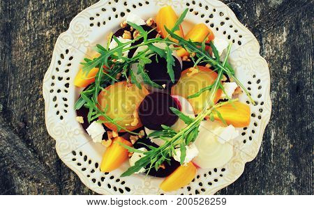 Healthy Beet Salad with red, white, golden beets, arugula, nuts, feta cheese on wooden background .