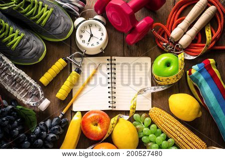 fitness concept with Exercise Equipment on wooden background.