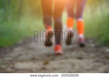 Blurred photo from bottom of two running sportswomen in forest