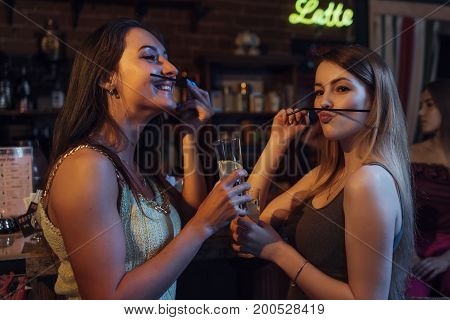 Girlfriends having a party holding glasses of cocktails, having fun, making moustache with straw in night club.