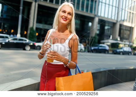 Photo of girl with packages by city buildings during day