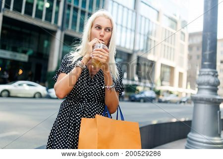 Photo of woman with drink, shopping near buildings in city during day