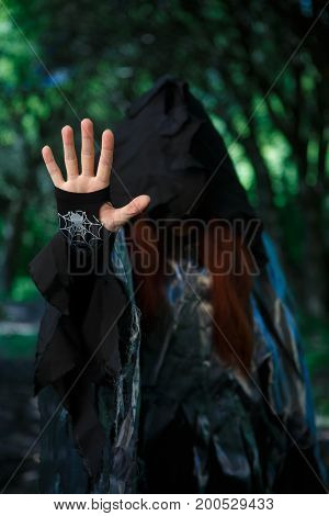 Photo of witch in hood with outstretched hand in forest