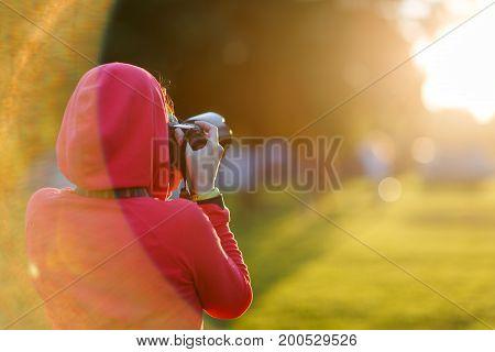 Photographer on blurry park background. Lensflare effect