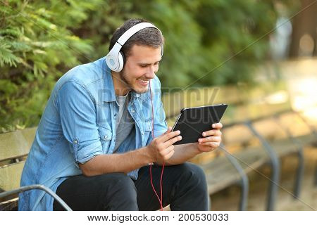 Portrait of a happy guy relaxing watching videos on line in a tablet sitting on a bench in a park