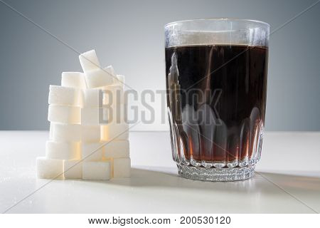 Glass Of Cola Drink And Heap Of Sugar Cubec. Unhealthy Eating Co