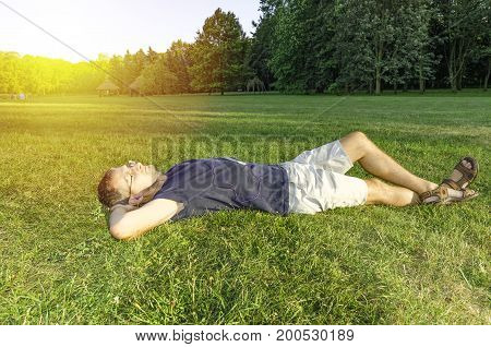 A man with a smartphone and headphones lying on the grass. Sunset glow in the background