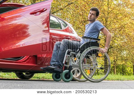 Disabled or handicapped man is trying to getting to car.