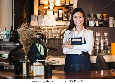 Asian Female Barista Wear Jean Apron Crossed Her Arms At Counter Bar With Smile Face,cafe Service Co