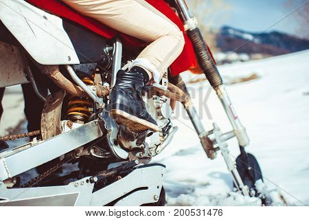Feet on the bottom of the motorcycle in winter