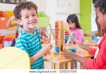 Kindergarten students smile when playing toy in playroom at preschool. international education concept.