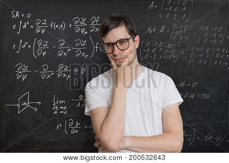 Young Student Is Solving Math Exam. Mathematics Formular On Blac