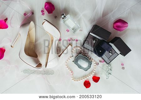 Tender beige wedding decorate shoes, wedding rings and necklace, top view