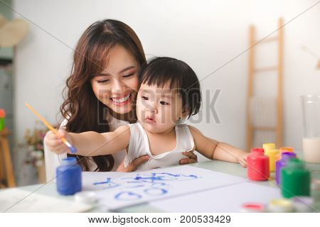Happy family mother and daughter together paint. Asian woman helps her child girl.