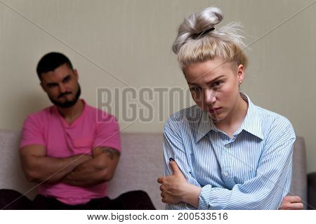 Depressed young woman looking at the camera while angry man sitting behind her. Unhappy couple having problems. Focus on female