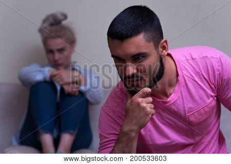 Young couple having relations problems. Unhappy woman sitting separately in sofa, while man looking down. Focus on male adult