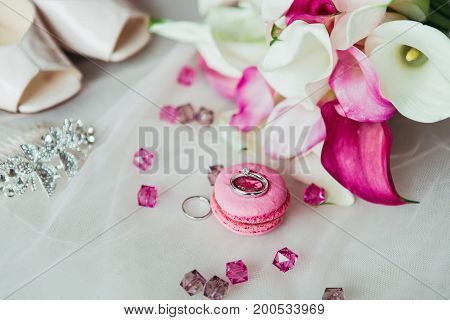 Wedding rings on the pink macaron with pink gems, shoes and flowers background