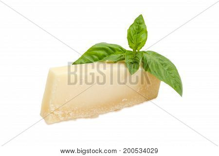 Piece of the parmesan cheese and twig of green basil on a white background
