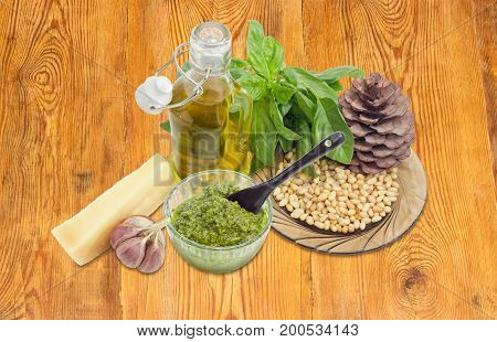Sauce basil pesto in the small glass bowl with small black ceramic spoon on a background of ingredients for its preparation and pine cone on a surface of an old wooden planks