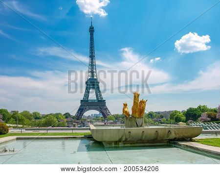 View of the Eiffel Tower from the Trocadero Square with fountain and sculptures in the foreground in Paris.