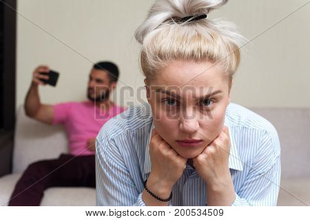Depressed young woman sitting separately and looking at the camera while her boyfriend using mobile phone. Couple Relations problems.