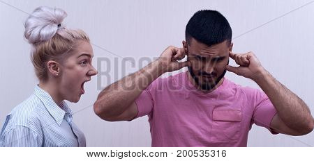 Family or couple relations problems. Young woman yelling at sad man while boyfriend covering his head with hands.