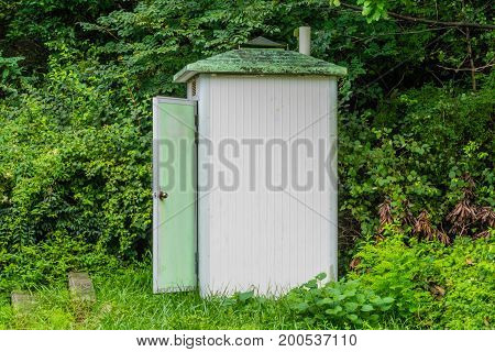 Old white public toilet with door open sitting at edge of a forested region on a mountainside in South Korea.