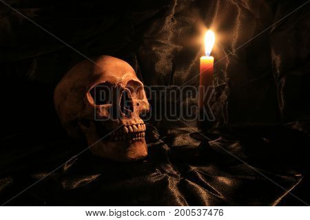 Still Life Of Skull  With Fetters And Candle On Black Fabric With Texture With Candle Light In Dim L