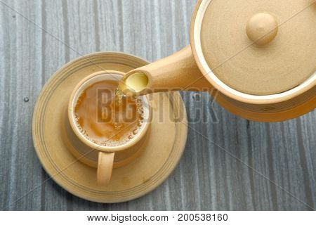Teapot pouring tea into a cup on a wood surface.