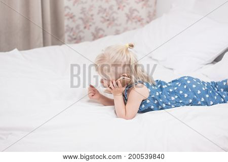 two year girl with blond hair with cellphon laing on bed