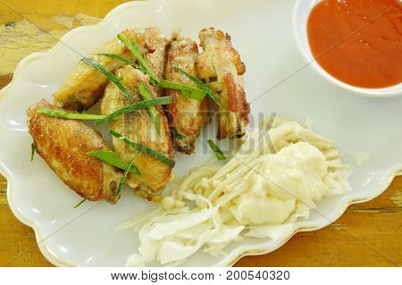 fried chicken wing salt and pepper topping slice lemon grass with boiled needle mushroom on plate