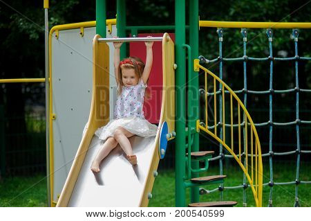 A cute little barefoot girly is playing on the playground. Baby is sitting on the children's slide. On the girl's head is a red wreath.