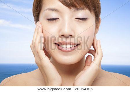 Beautiful Woman Face closeup and blue ocean background
